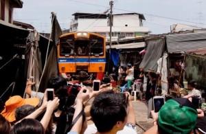 De trein rijdt dwars door de markt slechts enkele centimeters verwijderd van de marktwaar.